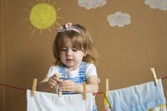 De kleine mooie meisjeshand die Wasknijper zetten en hangt uit om kleren te drogen Conceptueel huishoudelijk werk de baby helpt m royalty-vrije stock afbeeldingen