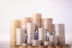 De kleine onderneming bemant cijfers die zich op Geldstapel bevinden royalty-vrije stock afbeelding