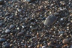 De kleine overzeese stenen op de de textuurachtergrond van strandkiezelstenen schitteren op de zonachtergrond stock foto