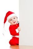 De kleine peuter die van de Kerstman van achter aanplakbiljet kijkt stock foto's