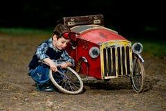 De kleine rode auto van de jongensreparatie Stock Foto's