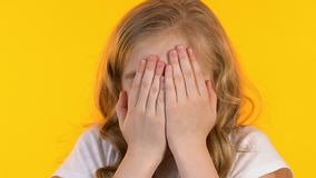 De kleine schoolmeisje sluitende ogen met handen, jong geitje is bang van enge film, close-up stock videobeelden