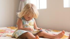 de kleine spelen van het blondemeisje met smartphone stock video