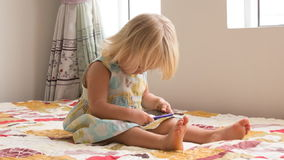 de kleine spelen van het blondemeisje met smartphone stock footage