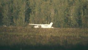 De kleine start van het propellervliegtuig voorbij gras en hittenevel stock footage