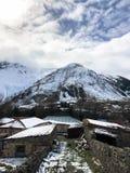 De kleine steenhuizen, gebouwen in het dorp op de mooie berg koude winter nemen met de de hoge mist en sneeuw van bergpieken zijn royalty-vrije stock fotografie