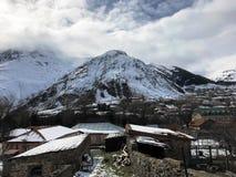 De kleine steenhuizen, gebouwen in het dorp op de mooie berg koude winter nemen met de de hoge mist en sneeuw van bergpieken zijn stock foto