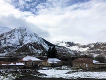 De kleine steenhuizen, gebouwen in het dorp op de mooie berg koude winter nemen met de de hoge mist en sneeuw van bergpieken zijn stock foto's