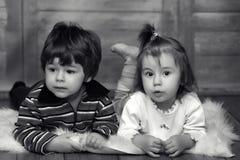 De kleine tweelingen liggen op de vloer stock foto's