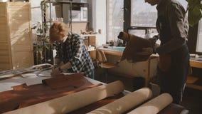 De kleine vakmanschap artisanale partners werken in met de hand gemaakt de productieproces van leergoederen samen in een workshop stock footage