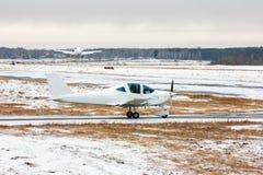 De kleine vliegtuigbewegingen op de taxibaan en achter vliegtuig gaat bij een koud de wintervliegveld van start Royalty-vrije Stock Foto's