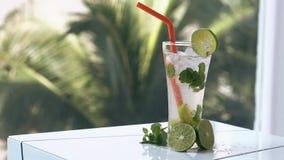 De kleine vlotter van ijsstukken in glas met koude mojitococktail stock videobeelden
