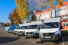 De kleine vrachtwagens, bestelwagens, koeriersminibussen bevinden zich op een rij klaar voor levering van goederen onder de voorw stock fotografie