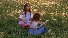 De kleine vrolijke zusters spelen in openlucht gitaar op paardebloemengebied, die tijd, Gelukkige kinderjaren gelijk maken concep stock video
