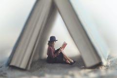 De kleine vrouw die die een boekwet lezen door een huis wordt beschermd maakte van een reuzeboek stock afbeelding