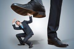 De kleine werknemer wordt misbruikt door grote werkgever stock afbeeldingen