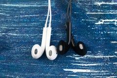 De kleine witte en zwarte hoofdtelefoons liggen op een blauwe denimachtergrond Horizontaal kader Royalty-vrije Stock Fotografie