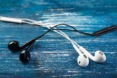 De kleine witte en zwarte hoofdtelefoons liggen op een blauwe denimachtergrond Horizontaal kader Royalty-vrije Stock Foto