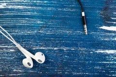 De kleine witte hoofdtelefoons en een zwarte stop liggen op een blauwe denimachtergrond Horizontaal kader Royalty-vrije Stock Foto