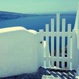 De kleine witte overzeese mening van de omheiningspoort en in Oia op Santorini-eiland, Royalty-vrije Stock Fotografie