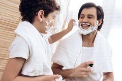 De kleine zoon smeert het gezicht van de vader met het scheren van schuim stock foto