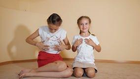 De kleine zusters die op vloer zitten en schilderen een t-shirt met hun handen stock videobeelden