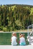 De kleine zusters zitten en bekijken het meer en het bosconcept stock foto