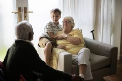 De kleinzoon is in een woonkamer met grootouders royalty-vrije stock foto's