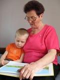 De kleinzoon en de grootmoeder lezen een boek stock fotografie