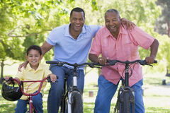 De kleinzoon en de zoonsfiets van de grootvader het berijden stock fotografie