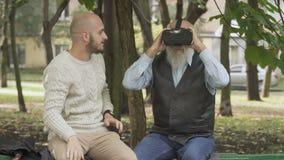 De kleinzoon geeft een grootvader proberen gebruikend een virtuele werkelijkheidsglazen stock video