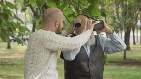 De kleinzoon met grootvader gebruikt een virtuele werkelijkheidsglazen in park stock footage