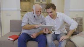 De kleinzoon onderwijst grootvader om digitaal tablet en Internet te gebruiken stock footage
