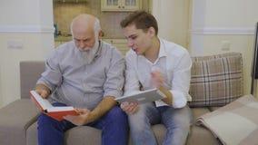 De kleinzoon onderwijst grootvader om digitale tablet te gebruiken stock video