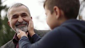 De kleinzoon raakt de mooie baard van zijn grootvader stock footage