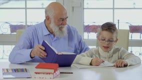 De kleinzoon van de grootvaderhulp om het huiswerk te maken stock footage