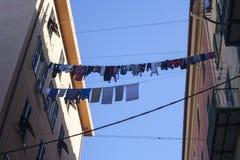 De kleren die tussen twee gebouwen in oh in de voorsteden Genua hangen stock foto