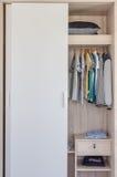 De kleren die van het jonge geitje in witte garderobe hangen Royalty-vrije Stock Afbeelding