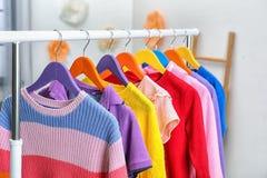 De kleren die van kleurrijke kinderen op garderoberek binnen hangen stock afbeelding