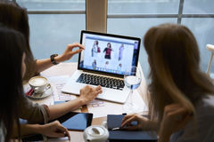 De kleren die van meisjesontwerpers coffeebreak in koffie samenwerken die laptop computer met spot op het scherm met behulp van royalty-vrije stock foto