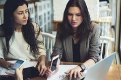 De kleren die van meisjesontwerpers samen het verklaren werken die vereisen en taken aan collega's via laptop computer aan wifi w Royalty-vrije Stock Foto