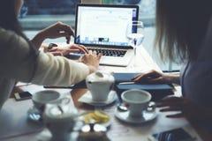 De kleren die van meisjesontwerpers samen voltooide video werken gieten tijdens theetijd gebruikend laptop met spot op het scherm royalty-vrije stock fotografie
