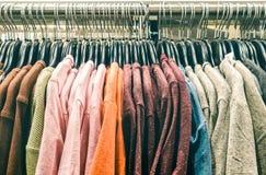 De kleren die van de tweede handtrui op winkelzuinigheid bij vlooienmarkt hangen royalty-vrije stock fotografie