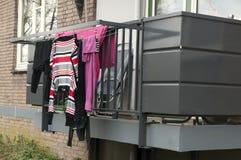 De kleren hangen om buiten een gebouw te drogen stock foto