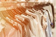 De kleren hangen op een plank in een ontwerper kleden opslag Stock Afbeeldingen