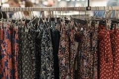 De kleren hangen op een plank in een ontwerper kleden opslag Stock Afbeelding