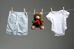 De kleren van de babyjongen, een teddybeer op de drooglijn stock afbeeldingen