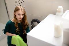 De kleren van de meisjeslading in wasmachine stock foto