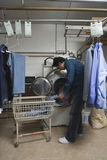 De Kleren van de mensenlading in Wasmachine bij Wasserij Stock Foto's