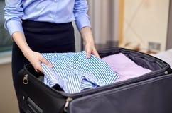 De kleren van de onderneemsterverpakking in reiszak Stock Fotografie